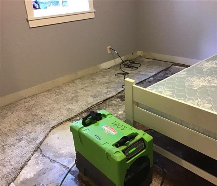 small dehumidifier drying a bedroom, carpet removed