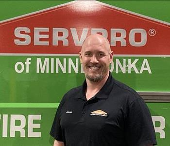 Jesse posing in front of a green SERVPRO van