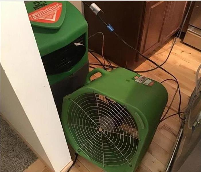 Our air mover and LGR dehumidifier sitting in a kitchen drying up water damage